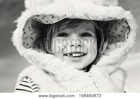 Closeup black-and-white portrait of cute adorable funny smiling laughing Caucasian kid baby girl in fur coat looking in camera. Happy lifestyle childhood concept. Child with missing tooth