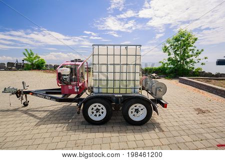 Toronto, Ontario, Canada, June 16, 2017, nice closeup view of a small trailer with plastic box in metal frame and engine mounted on trailer frame, Ontario place construction site, landscaping