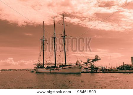 Toronto, Ontario, Canada, June 16, 2017, amazing view of old vintage classic cruise ship, frigate standing in lake Ontario waterfront on dark red pinkish background