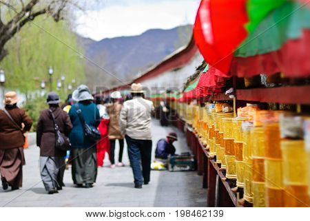 People walking near the golden prayer drums row in the street of Lhasa, Tibet background