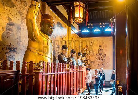 Shanghai, China - Nov 6, 2016: Inside the 600-year-old Old City God Temple. Visitors enter the main hall to pay respect. Statues of gigantic Taoist guards stand along the wall. Low-light image.
