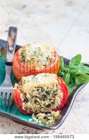 Baked tomatoes stuffed with quinoa and spinach topped with melted cheese on the plate vertical copy space