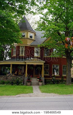 CADILLAC, MICHIGAN / UNITED STATES -  MAY 31, 2017: A red brick home with a wraparound porch and a turret in Cadillac's Courthouse Hill Historic District.