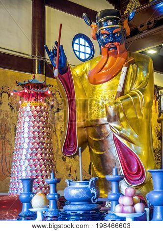 Shanghai, China - Nov 6, 2016: Inside the 600-year-old Old City God Temple. Statue of a Taoist Deity Judge with a scroll in hand that reminds visitors their deeds are