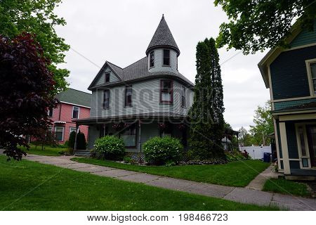 A gray Victorian mansion, with a wraparound porch and a turret,  and very tall sculpted arborvitae (Thuja occidentalis) plants, in the Courthouse Hill Historic District of Cadillac, Michigan.