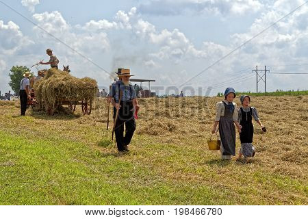 NEW HOLLAND PENNSYLVANIA - August 4 2017: Two young Mennonite girls with a pail and cup carry water for the hay crew at Big Spring Farm Days. This is an annual event demonstrating traditional threshing and harvesting methods using restored antique and vin