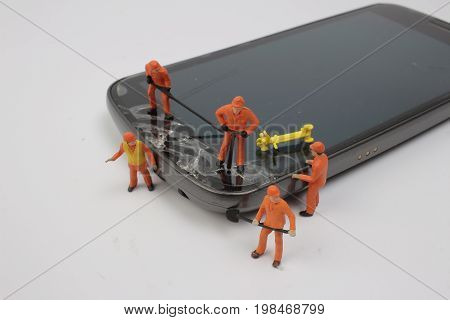 Miniature Workmen Inspecting Generic Cell Phone