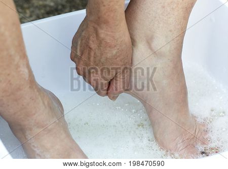 Middle Aged Woman's Feet In Soapy Water