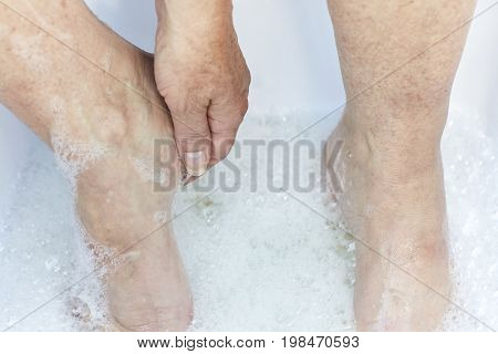 Middle Aged Woman's Feet In Water