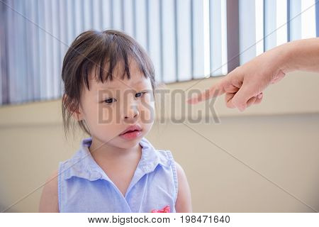 Little Asian girl feeling sad while parent scolding her at home