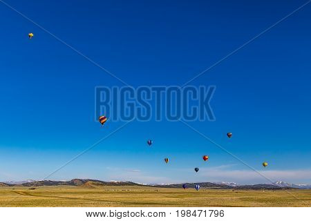With the Colorado Rocky Mountains as a backdrop hot air balloons take advantage of a clear early morning and an open rural field to practice taking off and touching down.