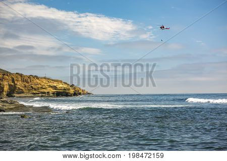 Us Coastguard Helicopter In Flight, Off The Coast Of Point Loma With A Person Hanging