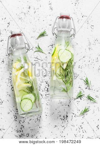 Rosemary lemon cucumber refreshing water in vintage bottles on a white background. Healthy refreshing lemonade