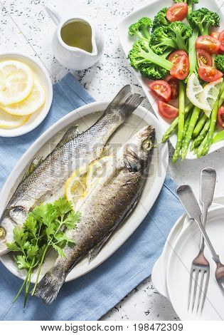 Baked sea bass and vegetables - broccoli asparagus tomatoes on a light background top view. Healthy balanced meal concept