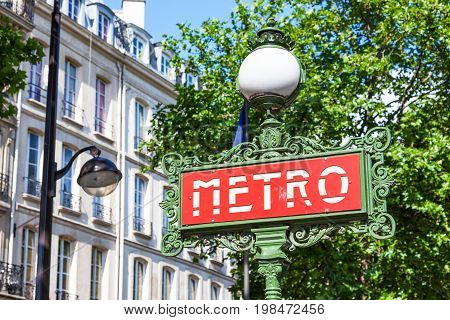 A Paris Metro sign crowned by a spherical lamp in the Art Nouveau style.