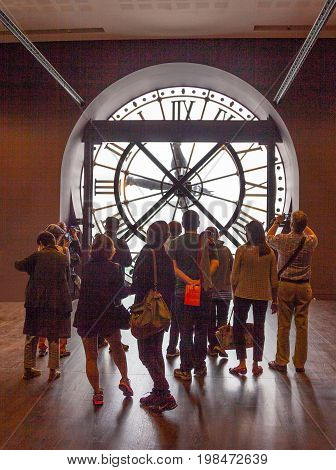 PARIS, FRANCE - JUNE 7, 2012: The famous clock inside the Musee d'Orsay in Paris France with a crowd in front of it. The museum houses the largest collection of impressionist and post-Impressionist masterpieces in the world.