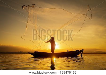 Silhouette of asian fisherman on wooden boat fisherman in action throwing a net for catching freshwater fish in nature river traditional fishermen at the sunset in thailand