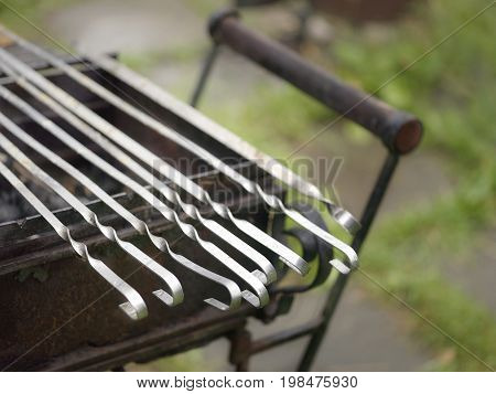 Bunch of metal barbecue skewers laid in the bbq trolley shallow depth of field closeup