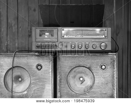 Vintage stereo center next to the wooden wall in black and white
