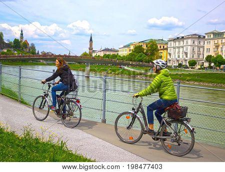 Salzburg, Austria - May 01, 2017: The female cyclist on the embankment in Salzburg, Austria on May 01 2017