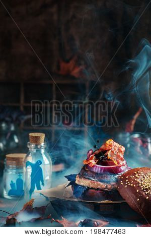 Hot Halloween party burger with smoke and scary silhouettes in glass jars on a dark background