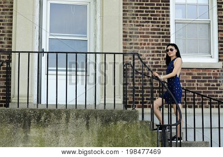 A chinese woman walking up cement steps to the door within a brick building on governors island in New York City New York.