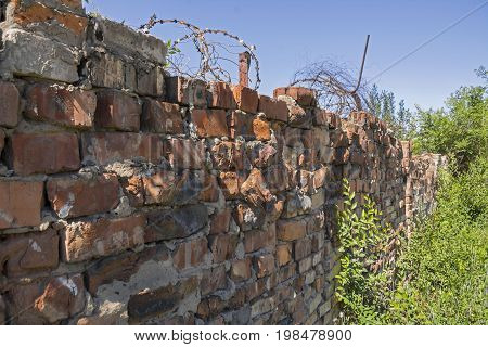 Old destroyed brick fence with barbed wire on field. Part of brick wall in ruins