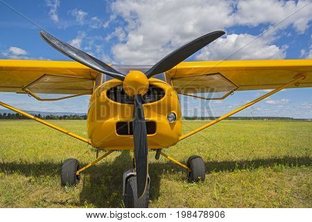 Light yellow airplane in grassy airfield. The propellers of aircraft close up