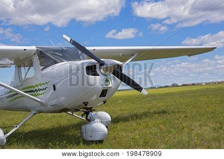 Small white airplane in the grassy field