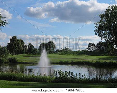 Water fountain or aerator in summer at golf course with interesting cloud from and trees in full bloom