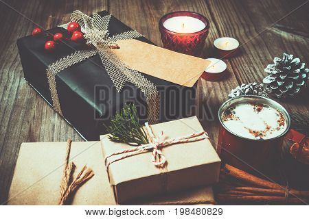 Christmas background with handmade present gift boxes and rustic decoration with candle hot chocolate on wood table in christmas night party. vintage color style.