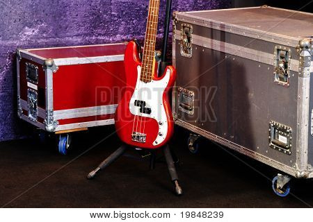 A red bass guitar and two cases on a stage