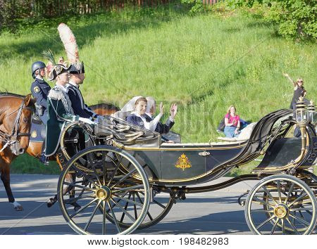STOCKHOLM SWEDEN - JUN 06 2017: The swedish queen and king Silvia and Carl Gustaf Bernadotte waiving to the audience from the royal coach on their way to celebrate the swedish national day.