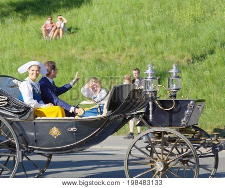 STOCKHOLM SWEDEN - JUN 06 2017: The swedish crown princess Victoria prince Daniel and princess Estelle Bernadotte smiling and waiving to the audience from the royal coach on their way to celebrate the swedish national day.