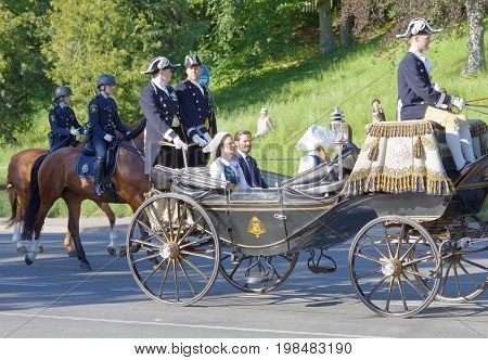 STOCKHOLM SWEDEN - JUN 06 2017: The swedish princess and prince Sofia and Carl Philip Bernadotte smiling and waiving to the audience from the royal coach on their way to celebrate the swedish national day.