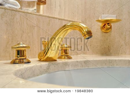 Gold tap in a marble bathroom
