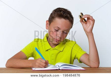 Portrait of tween boy sitting at the table, studying with book and holding fidget spinner toy. School education.