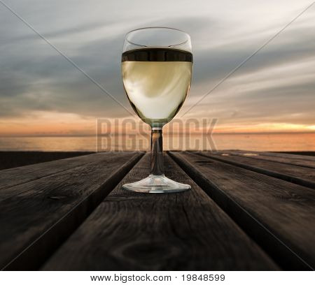 A glass of white wine at sunset next to the sea