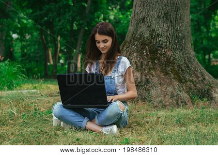 cutie young girl using a laptop and sits on a grass at the park