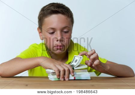 Portrait of 12 years old boy sitting at the table with dollar bills.