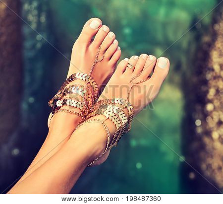 Tanned well-groomed feet amid tropical turquoise sea . Pedicure and foot Spa .Perfect clean female feet    . Spa ,scrub and foot care . Foot jewelry , payal.