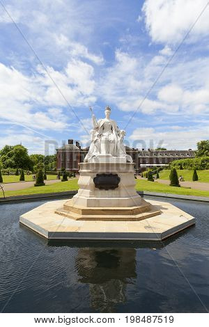 LONDON UNITED KINGDOM - JUNE 23 2017:Statue of Queen Victoria and Kensington Palace set in Kensington Gardens. It has been a residence of the British Royal Family since the 17th century and Queen Victoria's birthplace