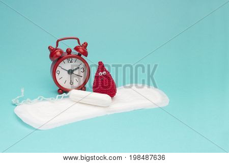 Red alarm clock, dreamy smile crochet blood drop daily menstrual pad and tampon. Woman critical days gynecological menstruation cycle. Medical conception photo. Menstruation sanitary woman hygiene