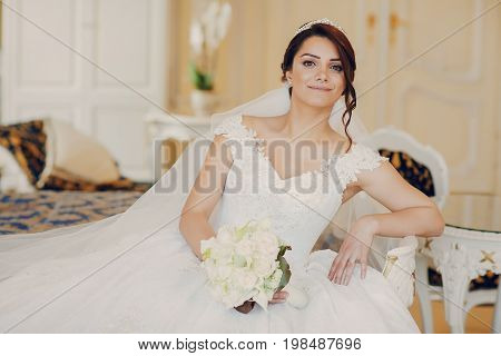 beautiful bride in a magnificent white dress and a crown on his head sitiing on a bad at home