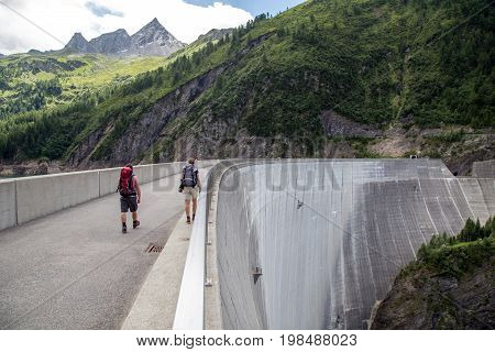 Blenio, Switzerland - July 14, 2017: Hikers on Luzzone arch dam in Ticino cantion