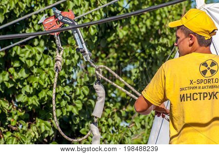 Ukraine Migea - July 30 2017: Zipline. The instructor prepares equipment for the ziplining. Starting platform on a high rock. Extreme and active rest.