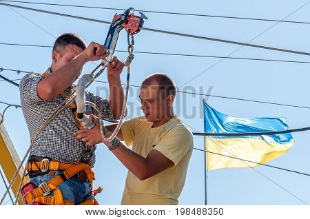 Ukraine Migea - June 30 2017: Zipline. The instructor conducts the instruction on safety of the next fan of an extreme. Starting platform on a high rock. Extreme and active rest.