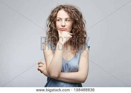 Portrait of beautiful casually dressed young Caucasian woman having doubtful expression looking away cunningly in indecisiveness holding her chin trying to find best solution. Body language concept.