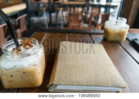 coffee iced coffee mocha and blur menu book on table wood background in cafe