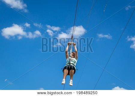 Ukraine Migea - July 30 2017: Zipline. A view of a man sliding on a steel cable against a beautiful blue sky with white clouds. Emotion of delight. Extreme and active rest.